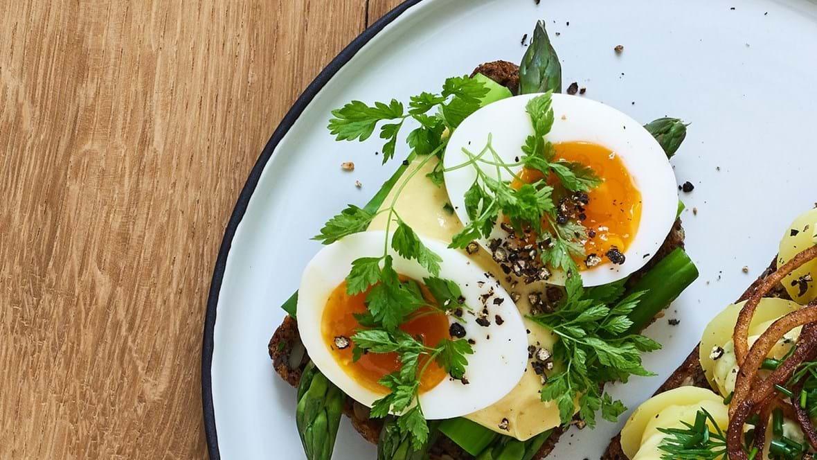 Klimavenligt smørrebrød med smilende æg, grønne asparges og hollandaise-mayo