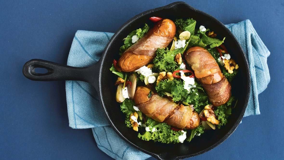 Baconsvøbte pølser og lynstegt grønkål med chili og valnødder