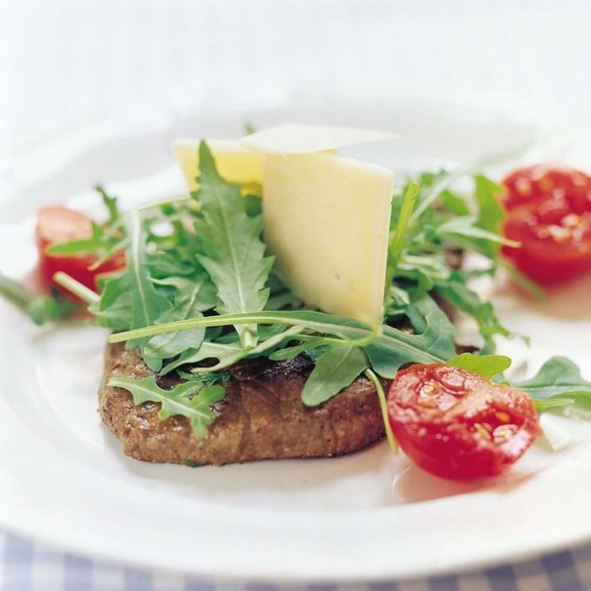 Steaks af kalveinderlår med rucola og frisk reven parmesanost.