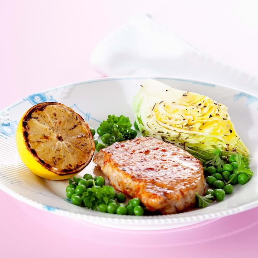 Grillet svinekotelet med spidskål og timian, ærter, persille og citron