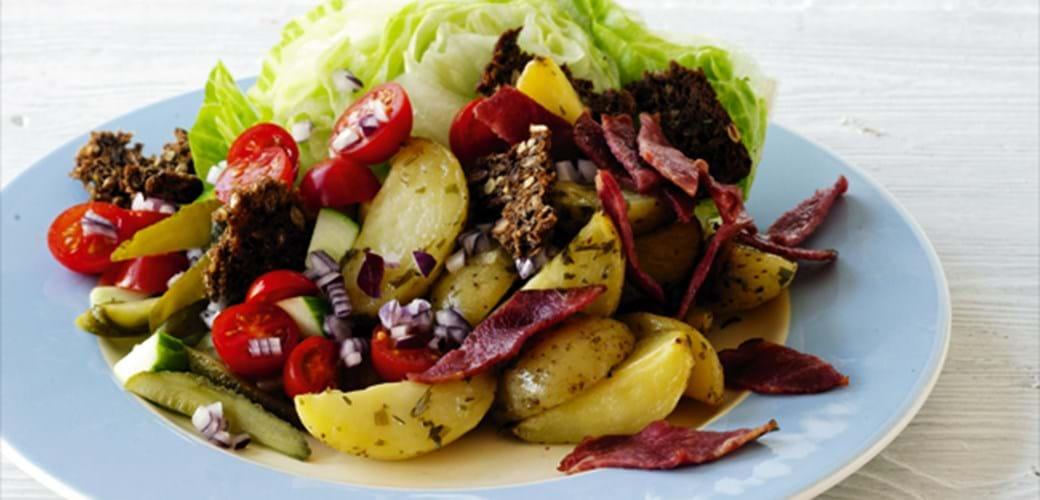 Burgersalat med bagte kartoffelbåde og grove croutoner
