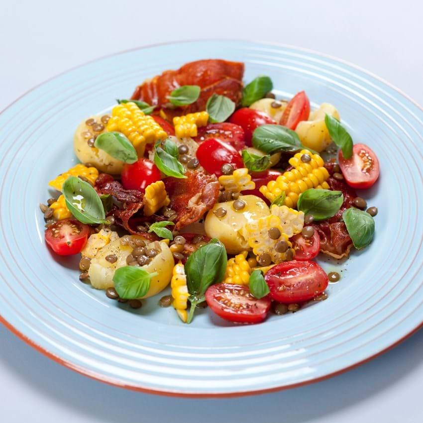 Knuste kartofler med linser, majs, tomater og sprød skinke