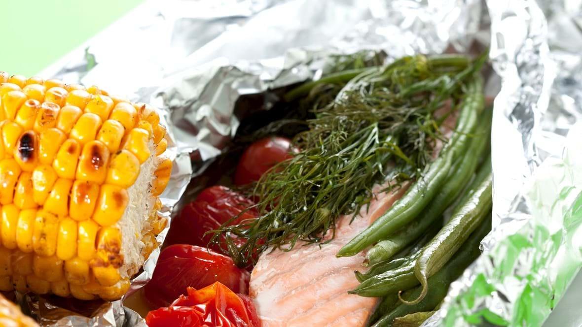 Laks i pakke med tomater, grønne bønner og dild og med grillede majskolber