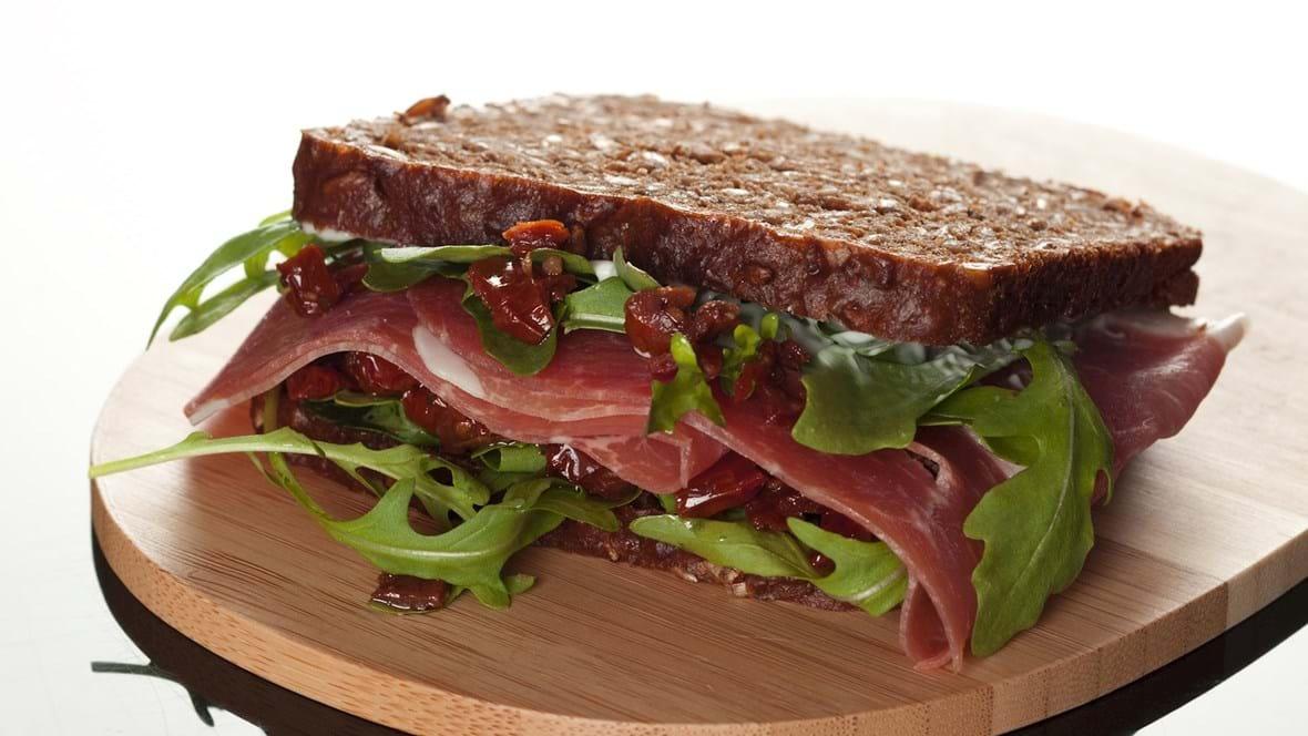 Rugbrødssandwich med lufttørret skinke, tomater og rucola