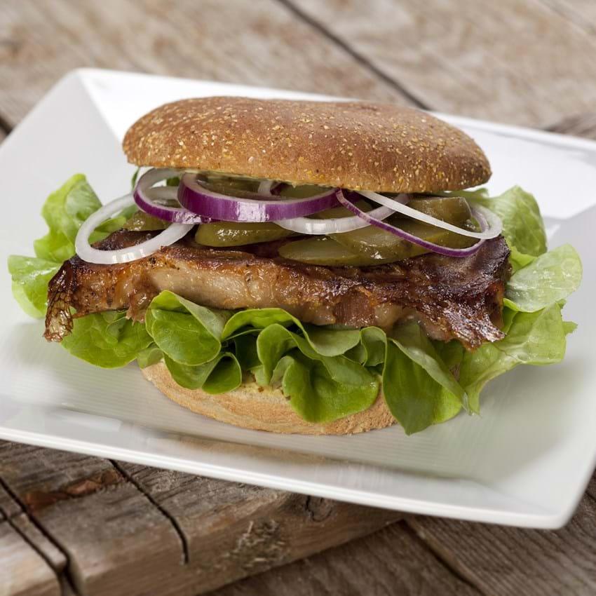 Sandwich med kold svinenakke, løg og syltede agurker
