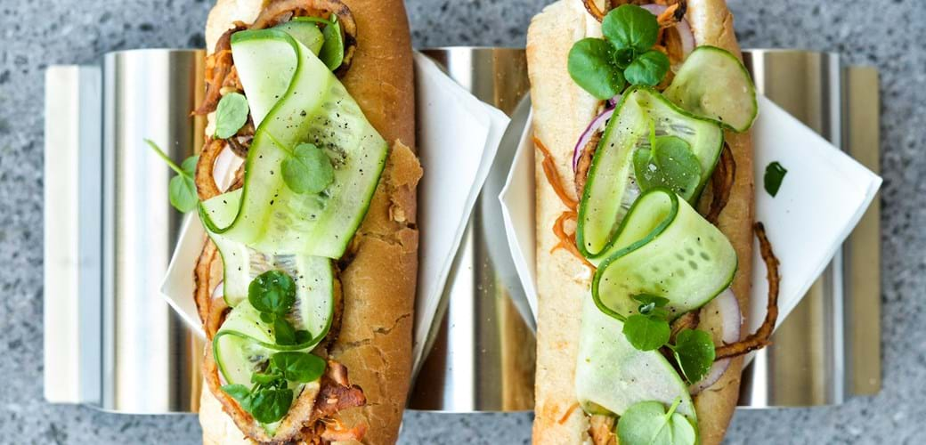 Pulled pork-hotdogs med hjemmestegte løg og syltede agurkestrimler