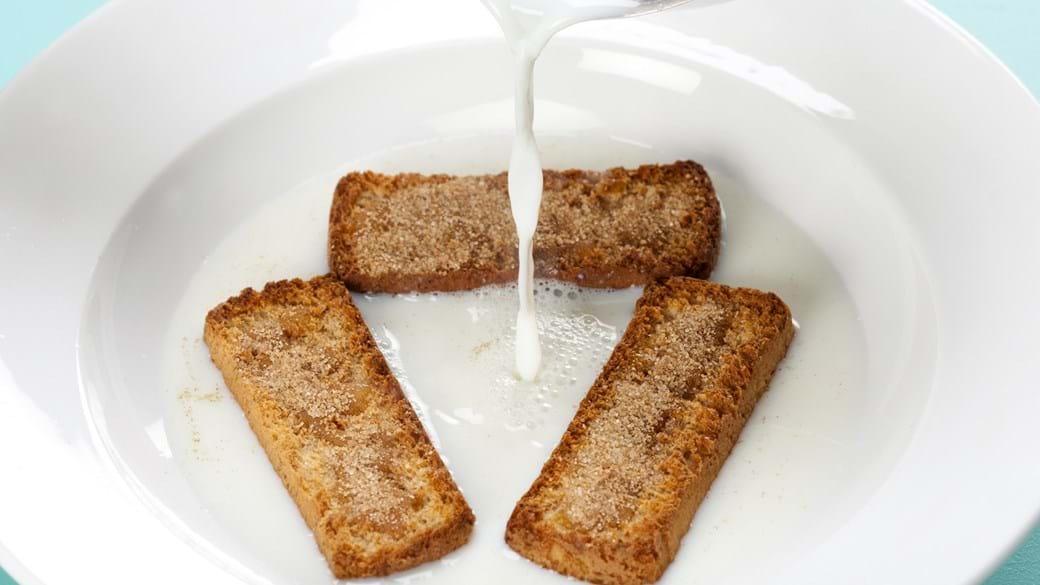 Varm mælk med tvebakker, honning og kanelsukker