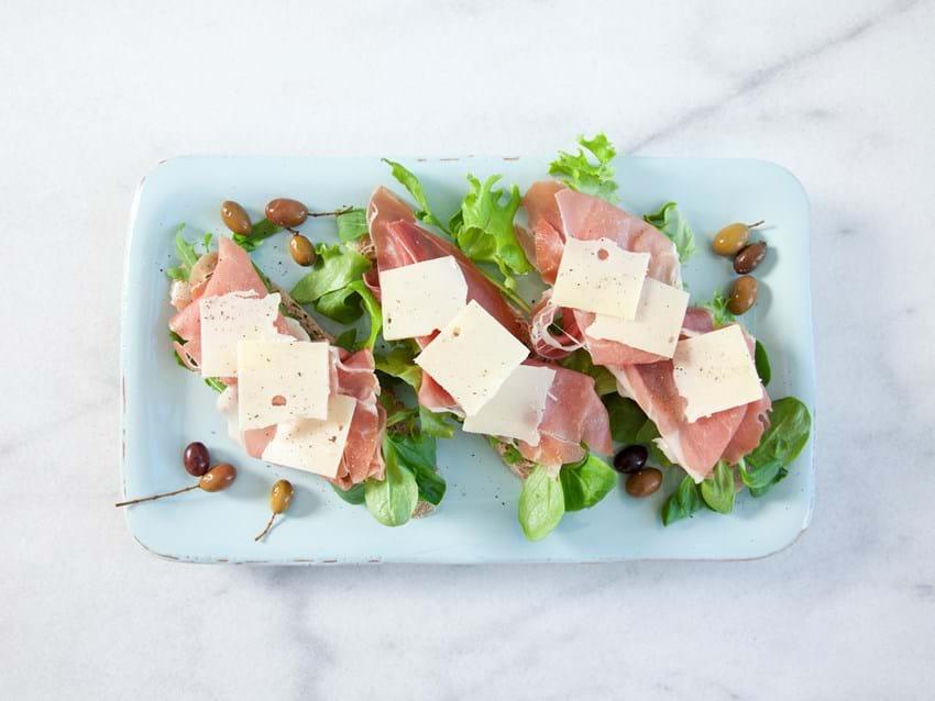 Bruscetta med salat, lufttørret skinke, ost og oliven